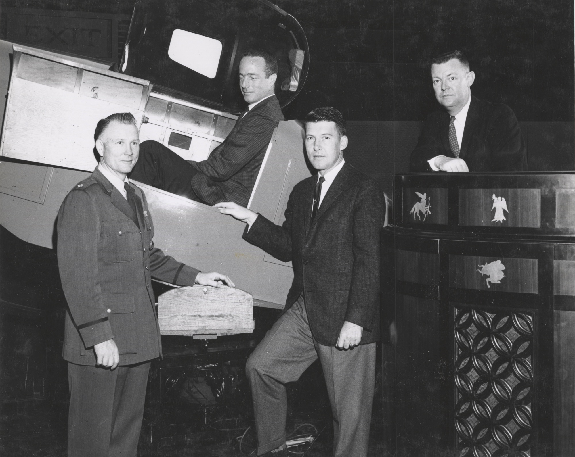 Photograph of Col. Cage, Scott Carpenter (in a Link trainer), Wally Schirra, and Morehead astronaut trainer James Batten. Photo courtesy of UNC Photographic Lab via Wilson Library digital collection.
